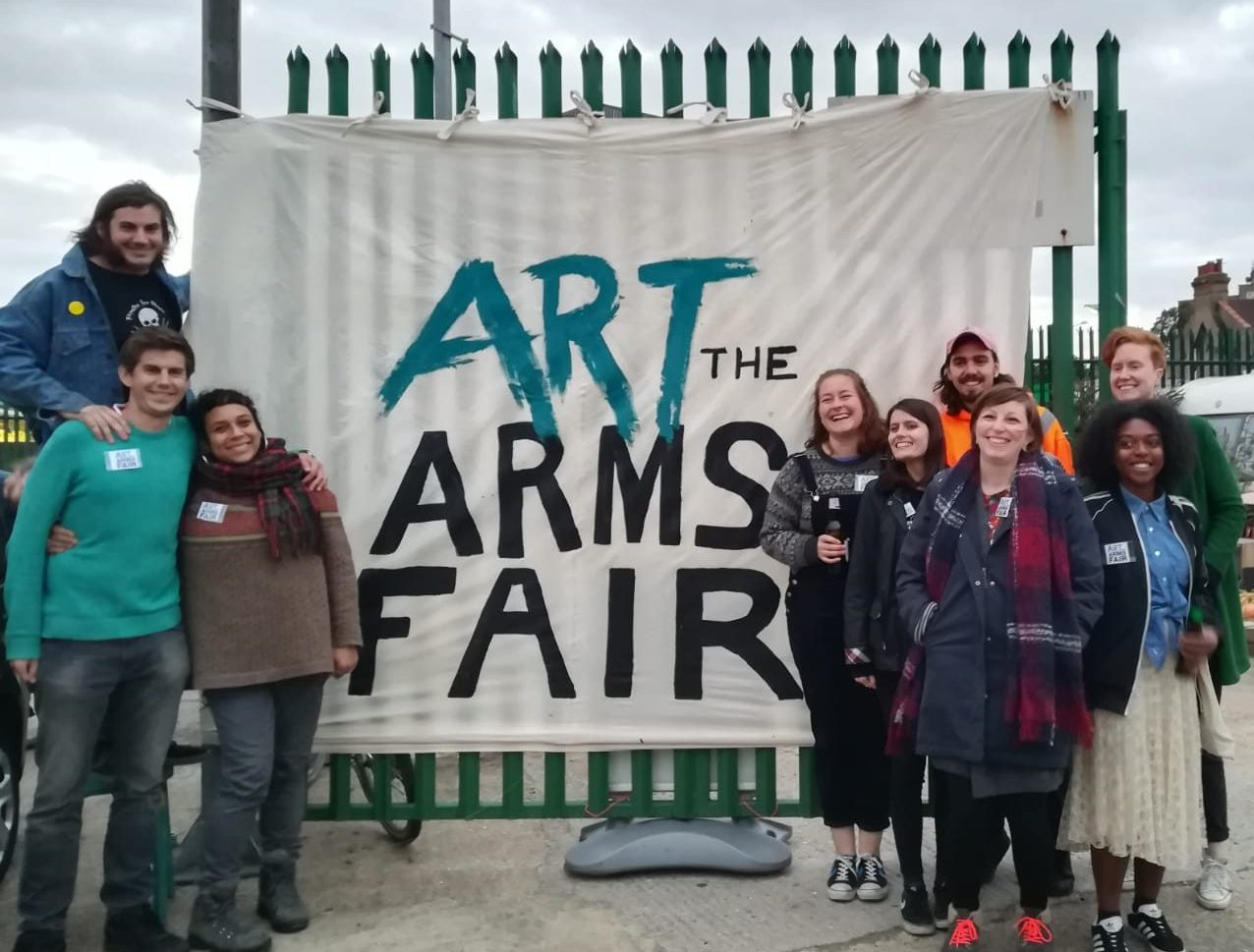 The ATAF stand next to a hand painted banner, smiling!