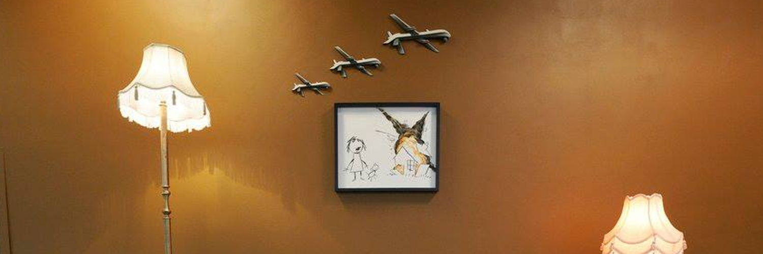Image of a work by Banksy - a 'child's' drawing of a house exploding and a child & dog running away. Three model drones hang above, and two lamps either side.
